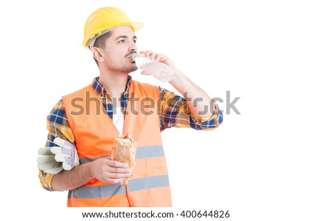 Portrait of young engineer eating a sandwich and drinking water as break snack concept isolated on white background - stock photo