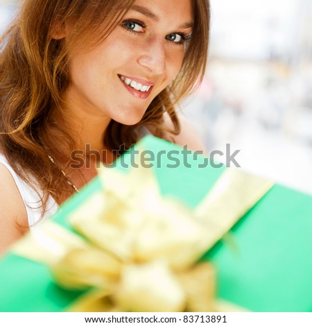Portrait of young excited pretty woman standing inside shopping mall smiling and holding christmas gift on foreground.