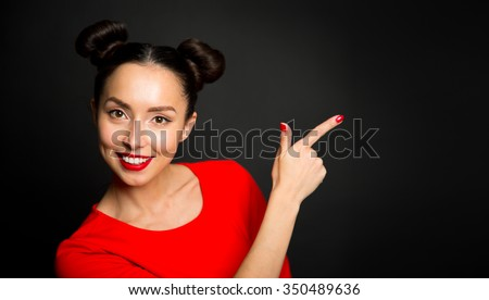 Portrait of young excited woman pointing forefingers over black background - stock photo