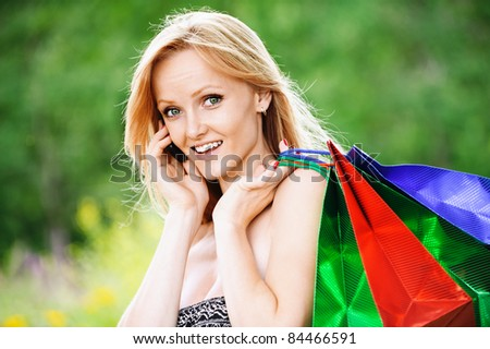 Portrait of young fair-haired pretty woman speaking on telephone and holding colourful bags at summer green park.