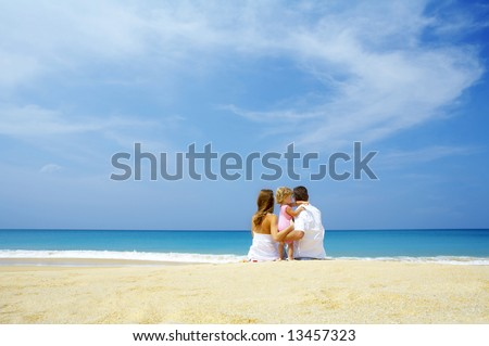 Portrait of young family having fun on the beach - stock photo