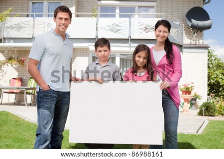 Portrait of young family holding a black white board outside their house - stock photo