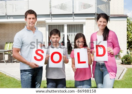 Portrait of young family holding a sold sign in front of their home - stock photo