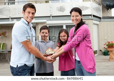 Portrait of young family of four holding a model of house - Outdoors - stock photo
