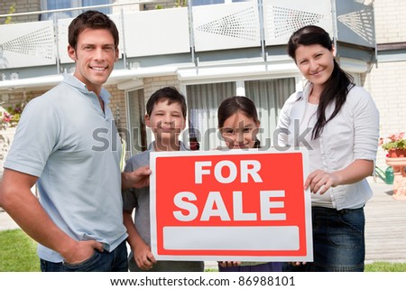 Portrait of young family selling their home holding for sale sign - Outdoors - stock photo