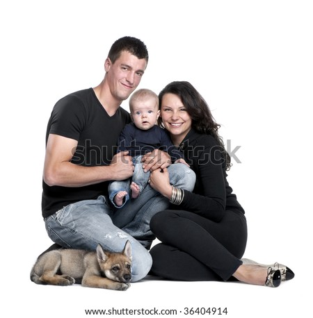Portrait of young family with baby boy and 2 months old wolf cub in front of white background, studio shot - stock photo