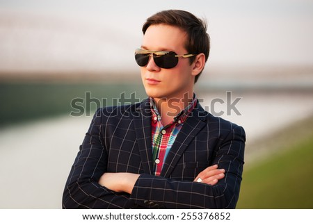 Portrait of young fashion man in sunglasses at sunset - stock photo