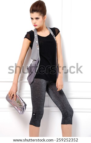 portrait of young fashion model holding purse posing in studio - stock photo