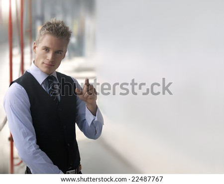 Portrait of young fashionable businessman pointing with lots of copy space