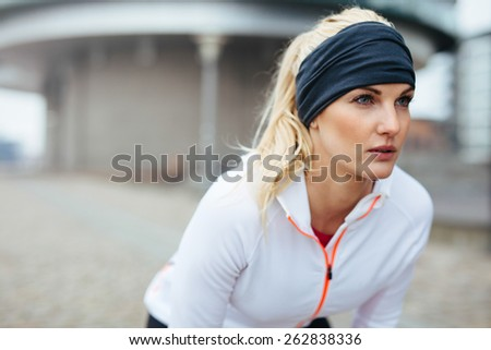 Portrait of young female athlete leaning over and looking away. Motivated and focused sporty woman before a run. - stock photo