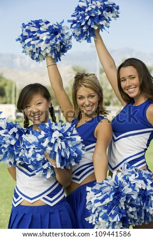 Portrait of young female cheerleaders holding pom-poms - stock photo