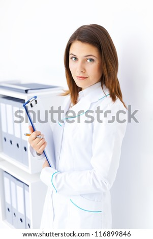 Portrait of young female doctor holding clipboard in hospital - stock photo