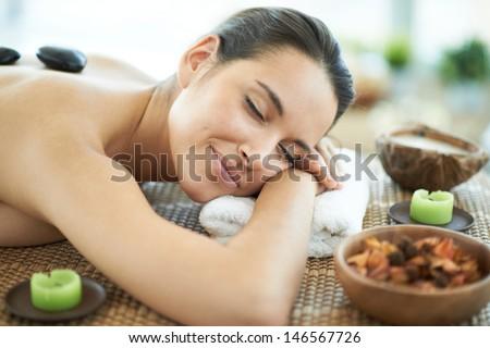 Portrait of young female enjoying spa procedure in beauty salon - stock photo