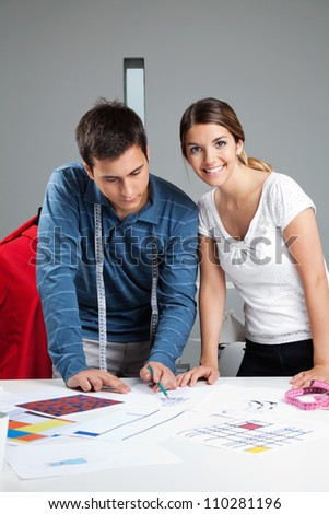 Portrait of young female fashion dressmaker with colleague working on rough outlines designs at workshop
