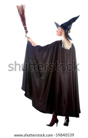 Portrait of young female in black hat and black clothing holding broom - stock photo