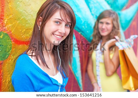 Portrait of young female listening music while friend standing in background with a shopping bag. Horizontal shot. - stock photo