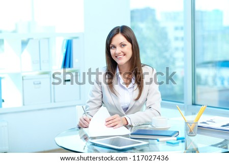 Portrait of young female looking at camera while checking proficiency test - stock photo