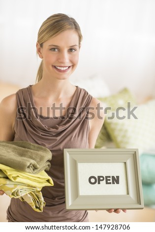 "Portrait of young female owner holding sheets and framed ""open"" sign in bedding store - stock photo"