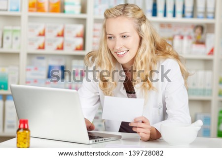 Portrait of young female pharmacist holding prescription while using laptop at pharmacy counter - stock photo