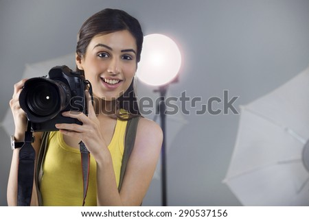 Portrait of young female photographer with digital camera in studio - stock photo