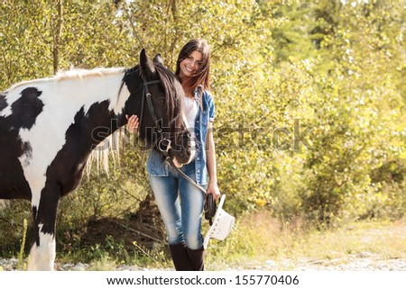portrait of young female rider smiling and embracing her horse outside  - stock photo