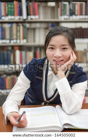 Portrait of young female student doing home work in front of library bookshelf