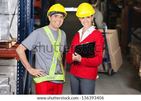 Portrait of young female supervisor holding clipboard standing with foreman in warehouse - stock photo