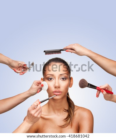 Portrait of young female surrounded by hands with beauty tools looking at camera - stock photo