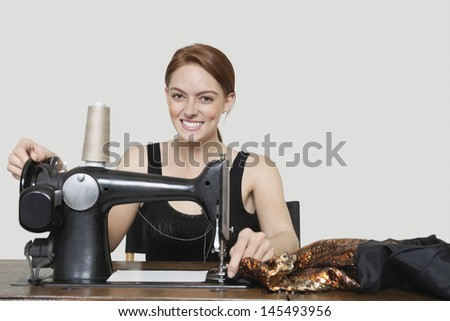 Portrait of young female tailor stitching cloth on sewing machine over colored background - stock photo