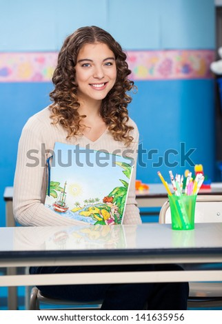 Portrait of young female teacher with book sitting at desk in kindergarten - stock photo