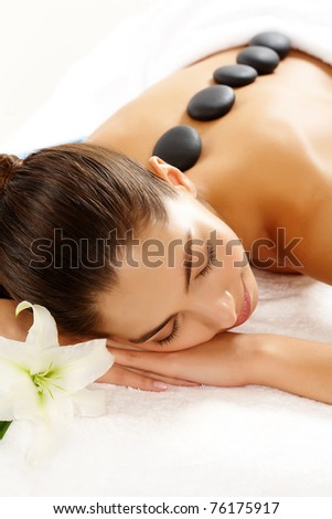 Portrait of young female with spa stones on back having massage - stock photo