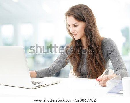 Portrait of young financial assistant working on business report while sitting at desk in front of laptop at office.