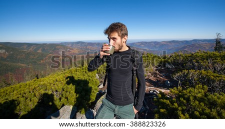 Portrait of young fit male hiker drinking tea on top of the mountain on a warm sunny day, autumn time. Beautiful overview point. Lifestyle and sport concept. - stock photo