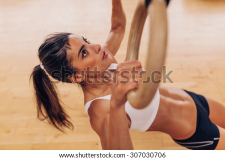 Portrait of young fit woman pulling up on gymnastic rings at gym. Muscular woman exercising with rings at health club. - stock photo