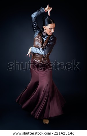 Portrait of young flamenco dancer in beautiful dress on black background. - stock photo