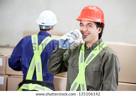 Portrait of young foreman drinking coffee while colleague working at warehouse