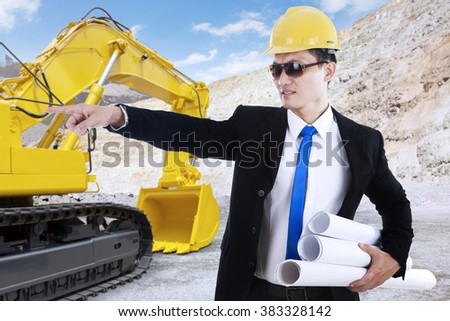 Portrait of young foreman holding blueprint and working in the construction site with excavator on the back - stock photo