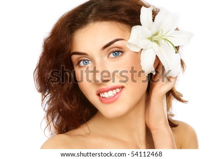 Portrait of young fresh beautiful smiling girl with clear makeup and white flower in hand