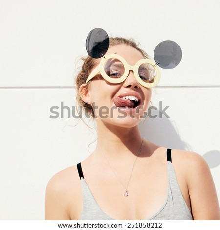 portrait of young funky woman showing her tongue. outdoors lifestyle - stock photo