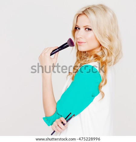 Portrait of young girl artist with brush for makeup