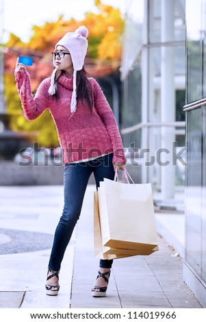 Portrait of young girl carrying shopping bag and holding credit card.