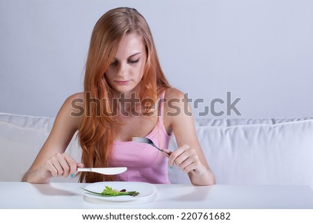 Portrait of young girl eating very small lunch - stock photo
