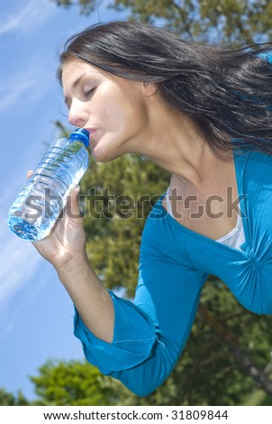 Portrait of young girl holding bottle of water in hand - stock photo