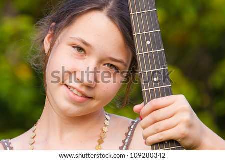Portrait of young girl holding guitar neck and smiling - stock photo