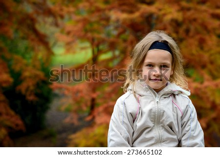 Portrait of young girl in the autumn park with natural light