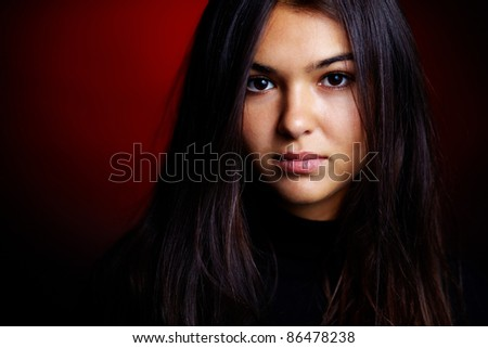 Portrait of young girl looking at camera in dark room - stock photo