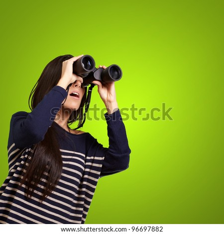 portrait of young girl looking through a binoculars over green - stock photo