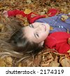 portrait of young girl on autumn leaves - stock photo