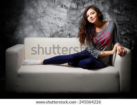 Portrait of young girl on sofa in dark room - stock photo