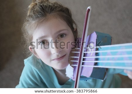 Portrait of young girl playing a toy violin for fun cute and beautiful - stock photo